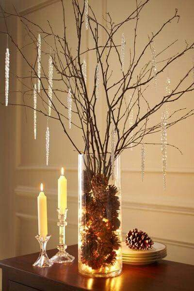 Glass vase filled with pinecones, tree branches and candles.