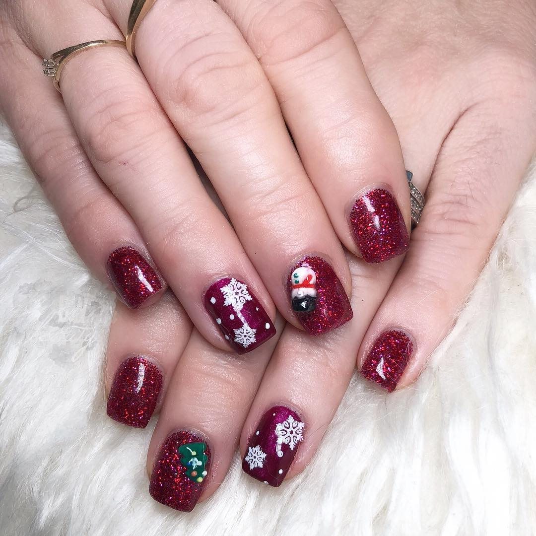 Glitter maroon gel nails with snowflakes, leaf and snowman.