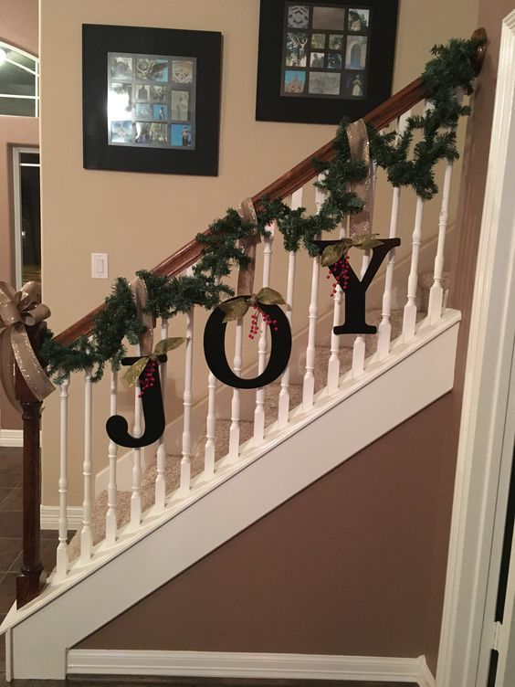 Greenery with big letter of JOY hanging on stairs.