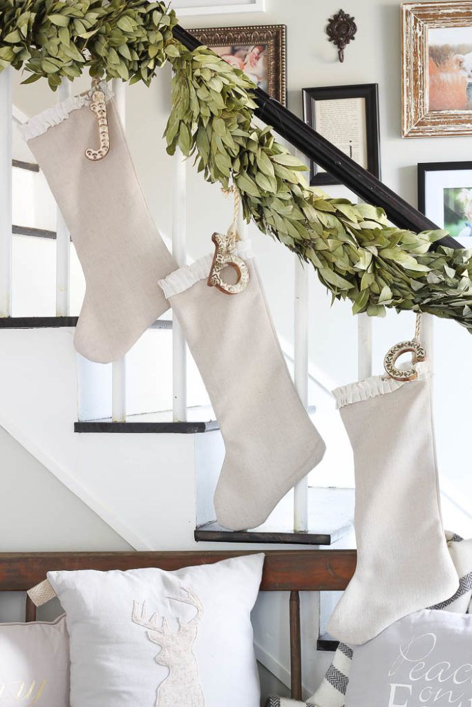 Hang white stockings on stairs with glitter letter and garland.