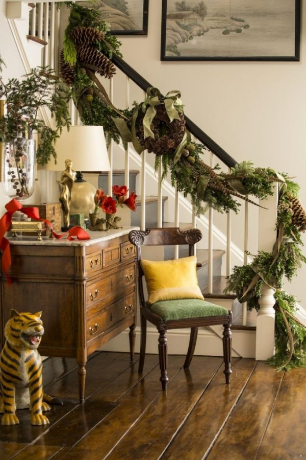Holly branches, fresh cut greens, pheasant feathers and giant pinecones wrap around banister.
