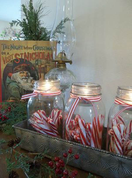 Mason jars filled with candy cane in galvanized metal tray.