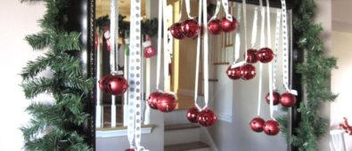 Mirror is decorated with garland and red ornaments.