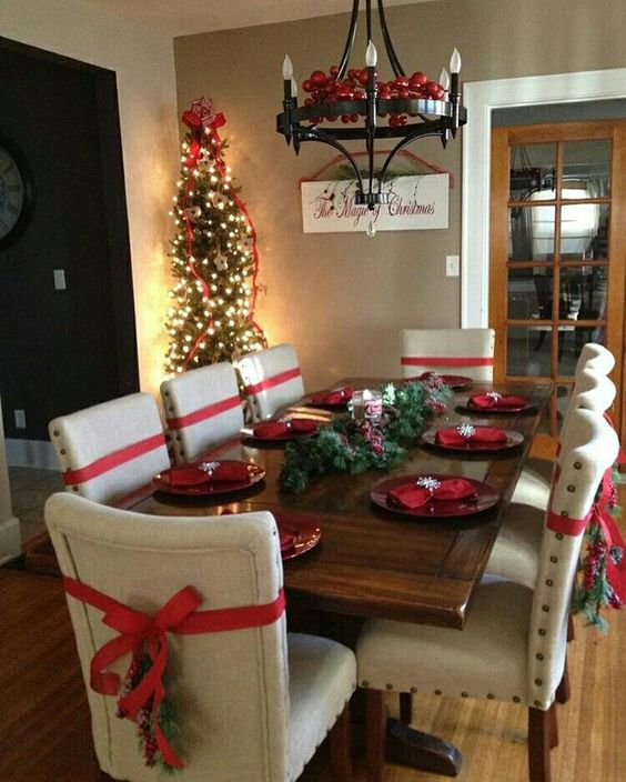 Nice Christmas table decoration with red bow at chairs.