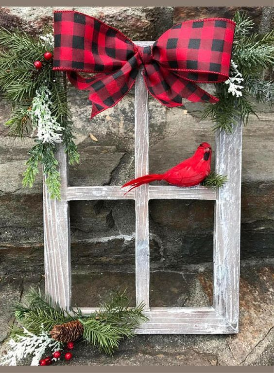 Old wooden frame is decorated with pinecone, cherries and bird for outdoor decoration.