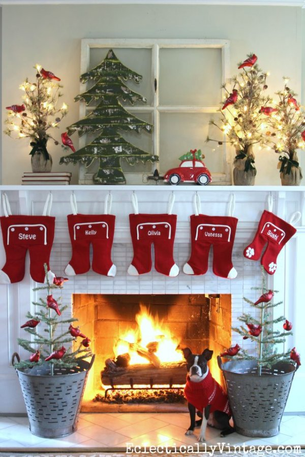 Personalized stockings, red cardinal-decorated plants and wooden tree.