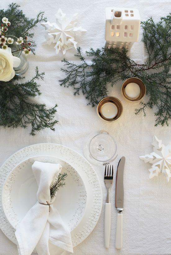 Pinecone leaves and candle with white cutlery.