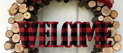 Plaid welcome on wooden wreath for Christmas.