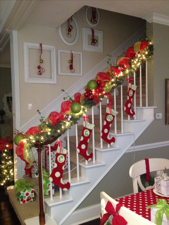 Polka dots stocking tied to railing with ribbon, small ornament hung on antique picture frames and red & green burlap rolled around railing.