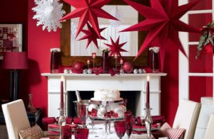 Red & white table setting with big stars, ornaments and candles for festive season.