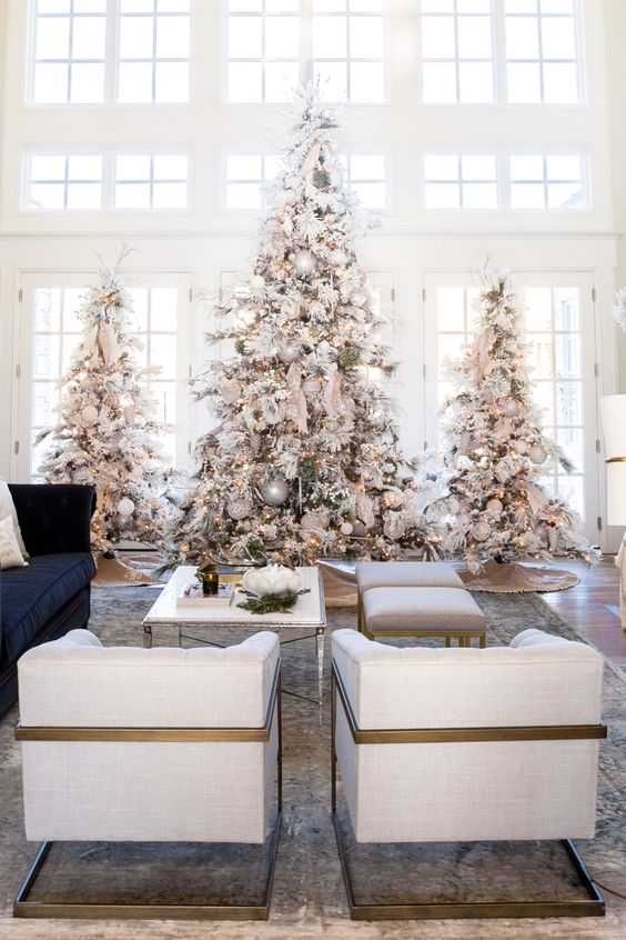 Rocking white Christmas tree in living area with silver & golden ornaments.