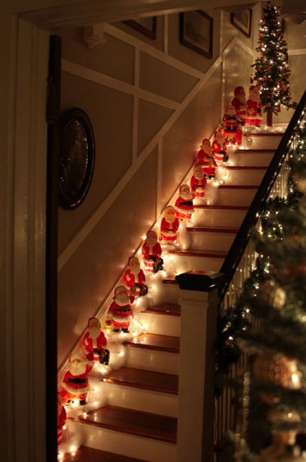 Santa clause is standing at each stairs and decorated with lights.
