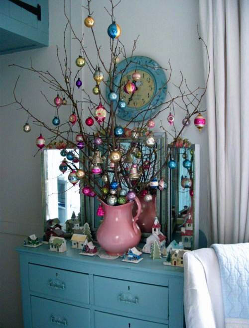 Sensational tree branches with colorful ornaments in pink vase.