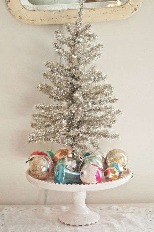 Silver Christmas tree with colorful shabby ornaments.
