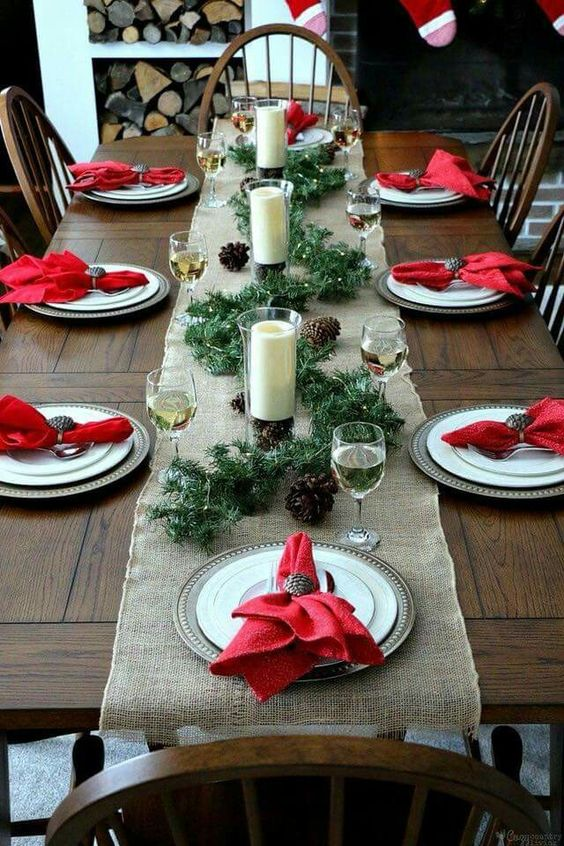 Simple Christmas table setting with red napin, candles and pinecones.