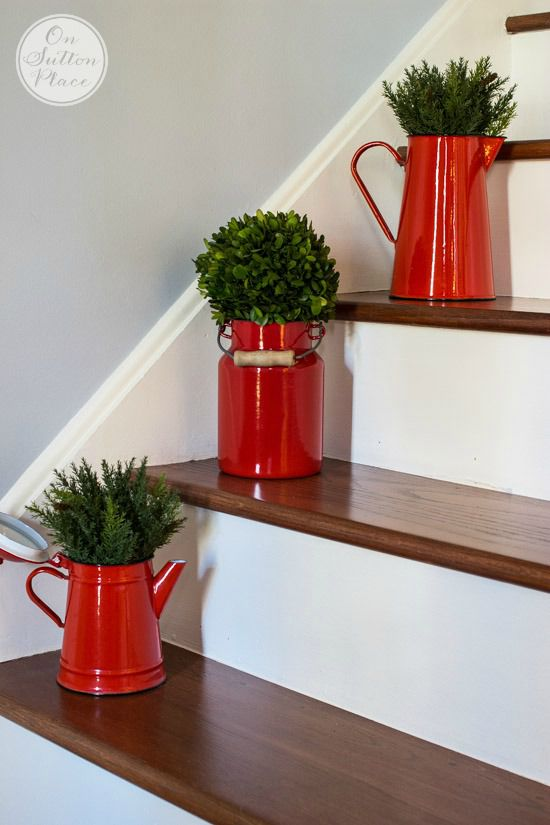 Vibrant red pitcher with greenery on each step.
