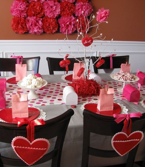 Awesome red and pink table decor with hearts hanging on chair for romantic lunch date.