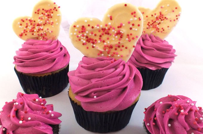 Bright pink cupcakes with heart topping.