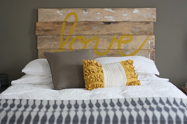 DIY love sign headboard made from an old fence with mustard ruffled pillow.