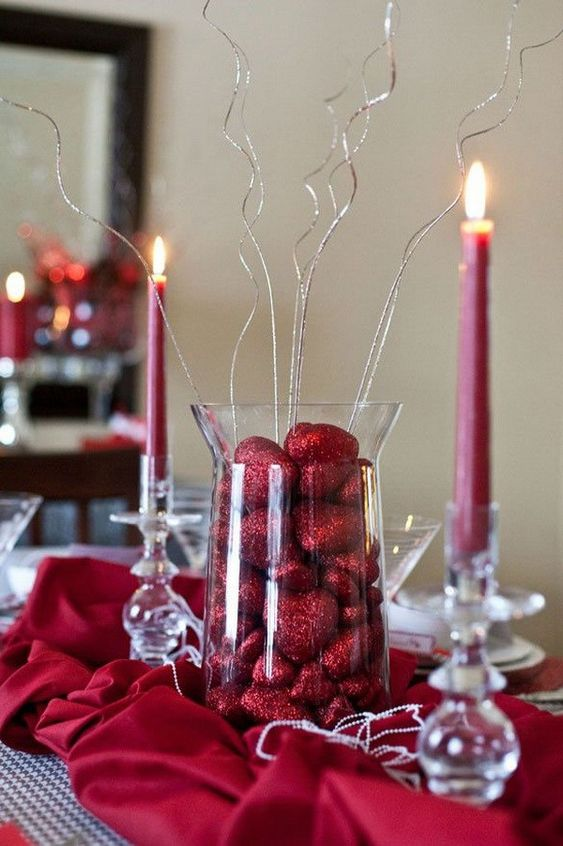 Glass vase filled some red heart shaped chocolates with red candles.