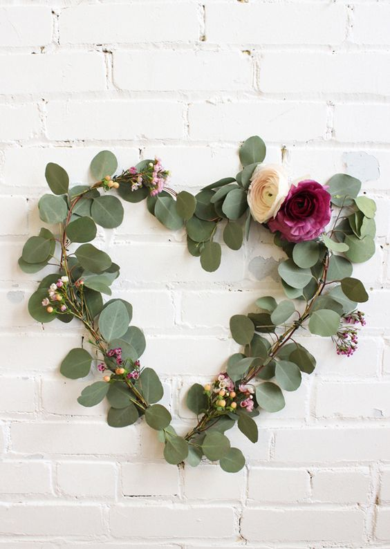 Heart shape wreath of fresh leaves and flowers.
