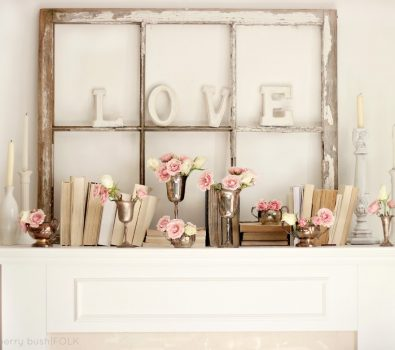 Old frame used to decorate mantel with pink flowers.