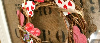 Playing card in heart shape arranged in wreath.