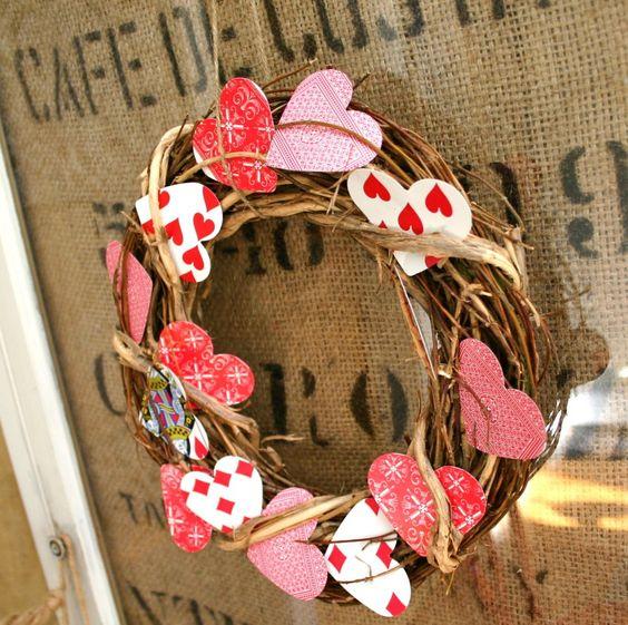 Playing card in heart shape arranged in wreath.