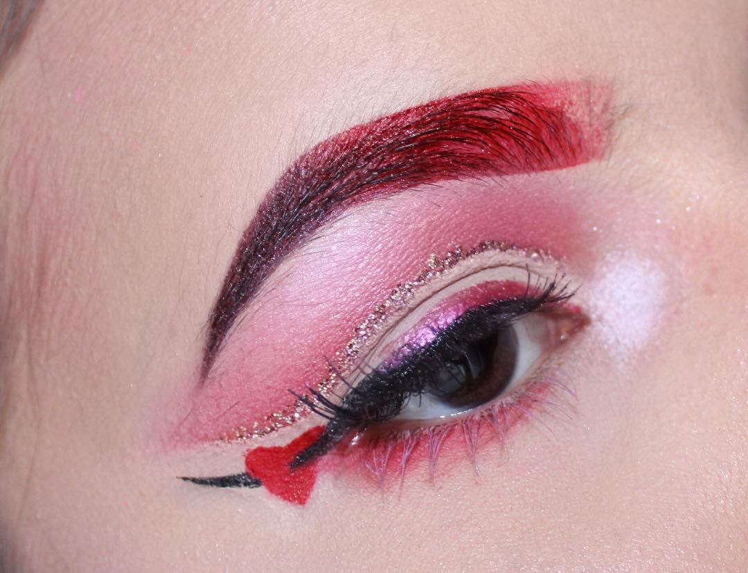 Red brows with glitter makeup and hanging heart.