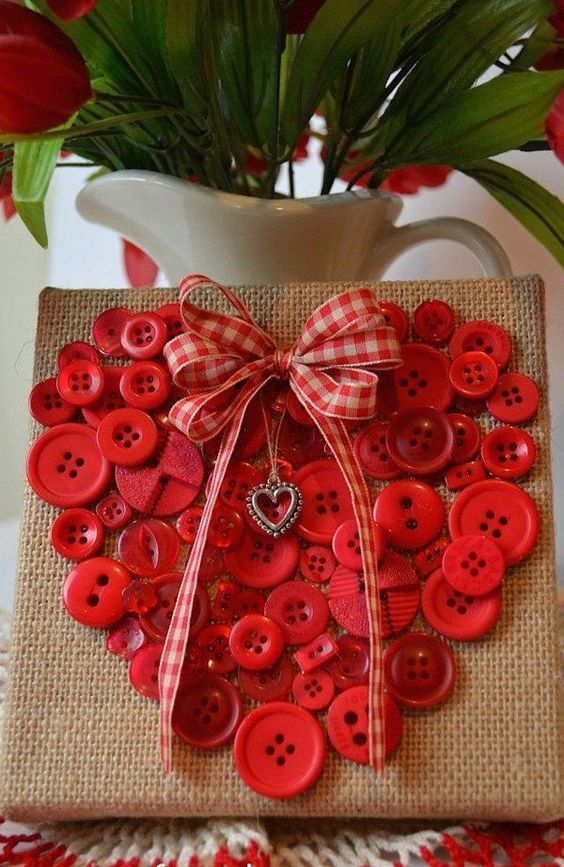 Red buttons in heart shape on burlap.