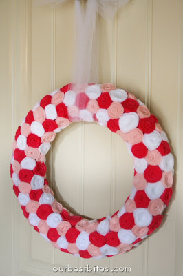 Red, pink and white rosette v-day wreath on white door.