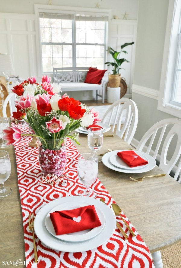 Sassy red and white table setting with envelope napkin fold.