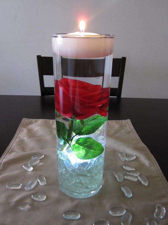 Simple rose in a clear vase topped with a white floating votive.