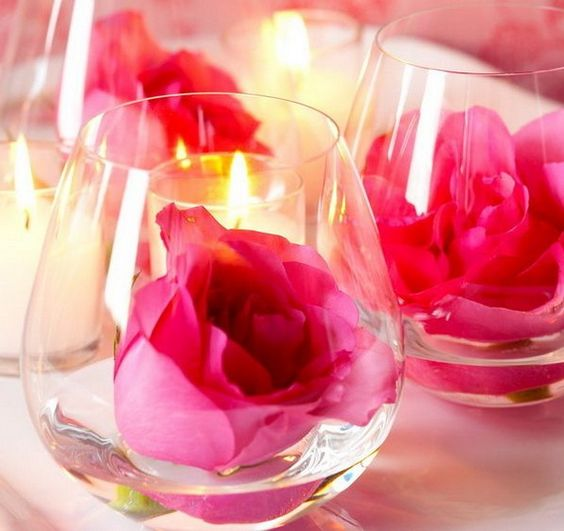 Stemless wine glass candle holder with fresh flower.
