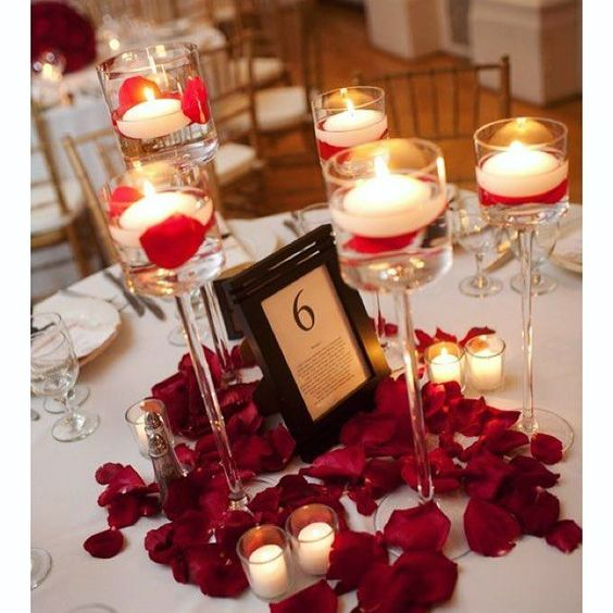 Valentines day table is decorated with petals and candles.