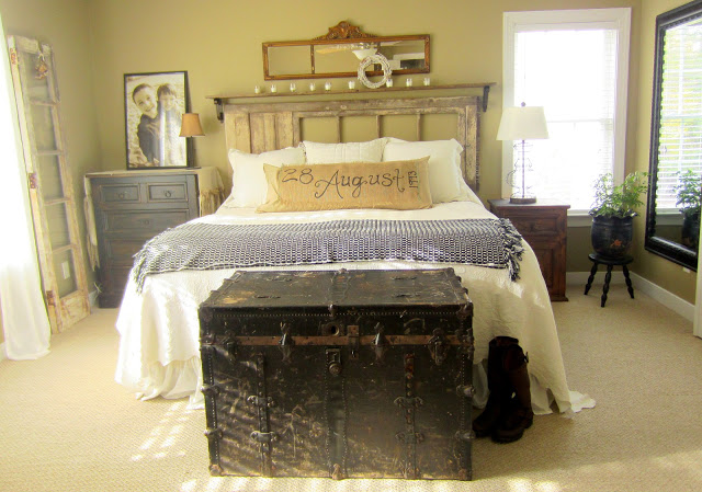 Vintage style bedroom decor with old trunk, wedding anniversary date on burlap pillow cover and wall art.