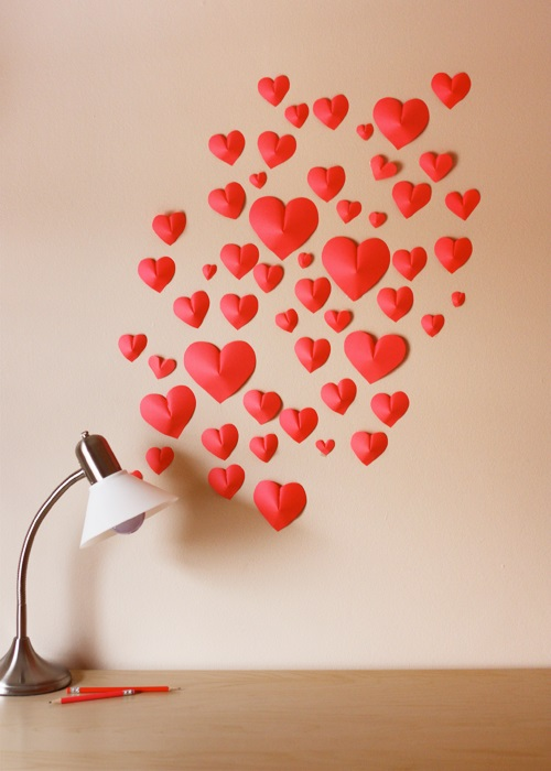 Wall is decorated with different size of paper hearts.