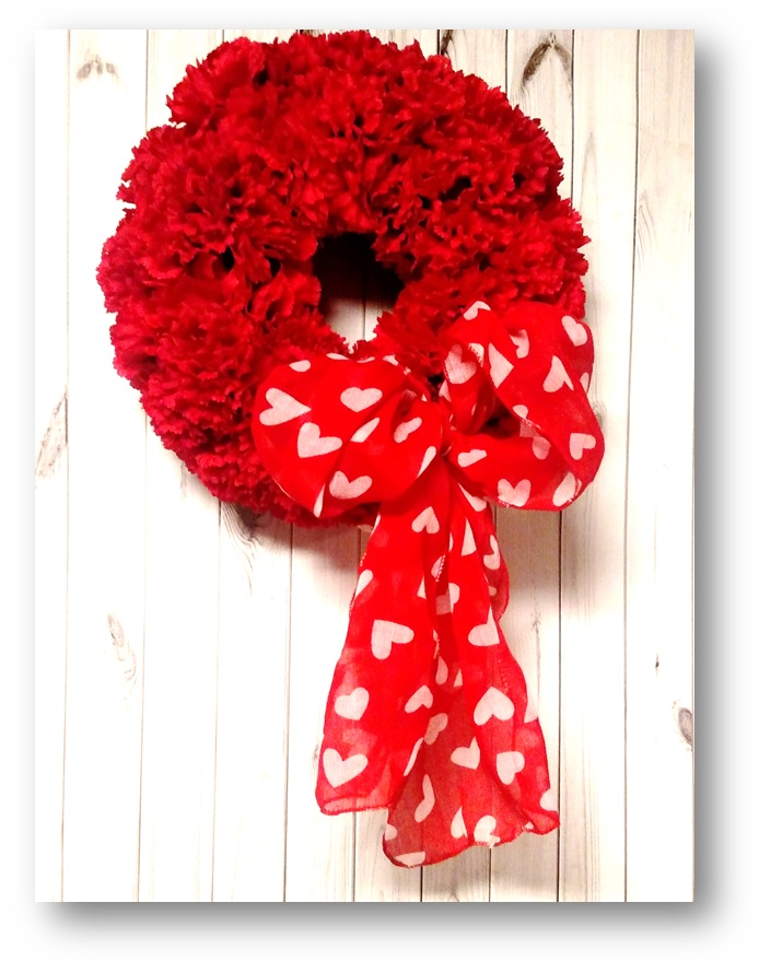 Carnation wreath with heart print ribbon.