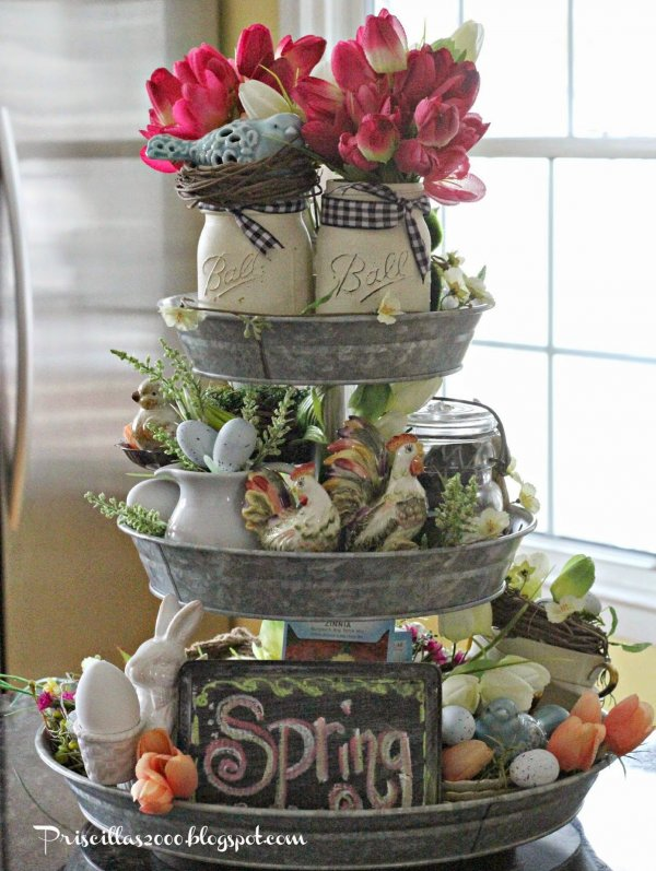 A galvanized tiered tray filled with nest, eggs, mason jar with tulips.