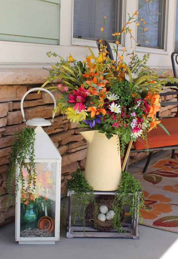 Beautiful watering can and lantern floral display at porch.