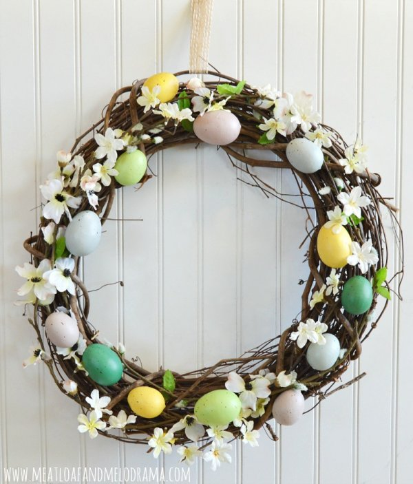 Charming twig wreath decorated with flowers and eggs.