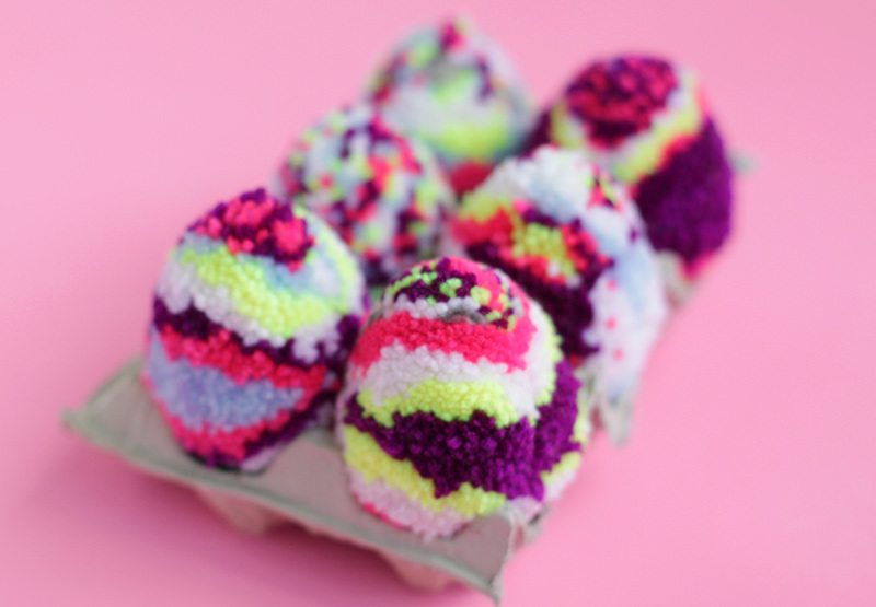Multicolored diy pom pom Easter eggs.