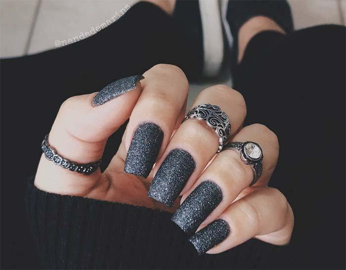 Black holiday nails with silver sparkles.
