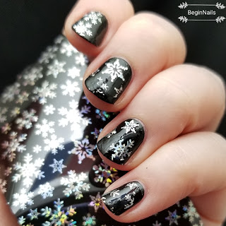 Black holographic Christmas snowflake nails.