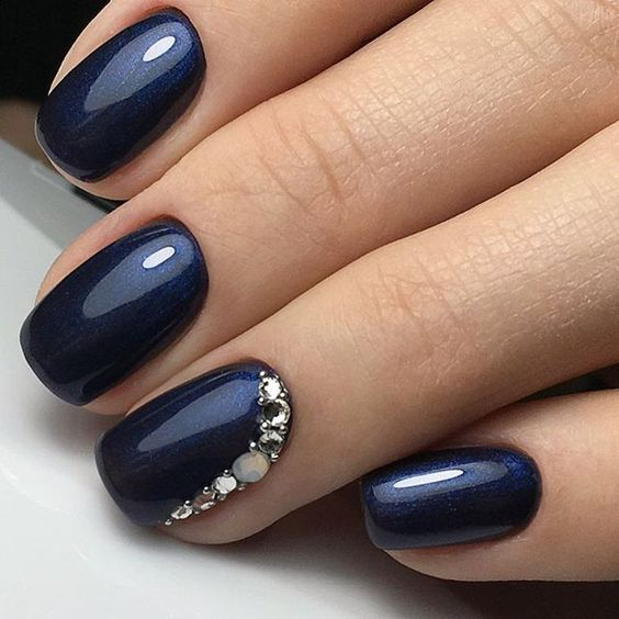Dark blue jewel studded 3D nails.