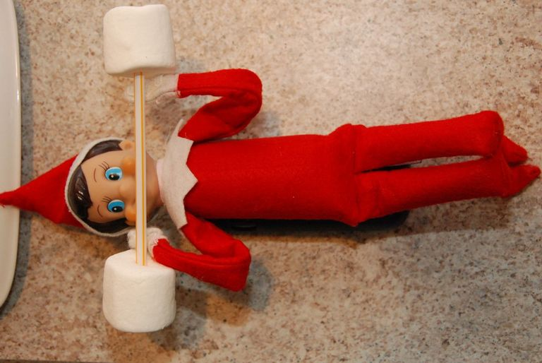 Elf on shelf doing workout with marshmallow dumbbells.
