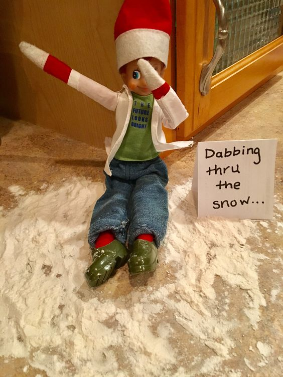 Elf on the shelf dabbing through the snow.