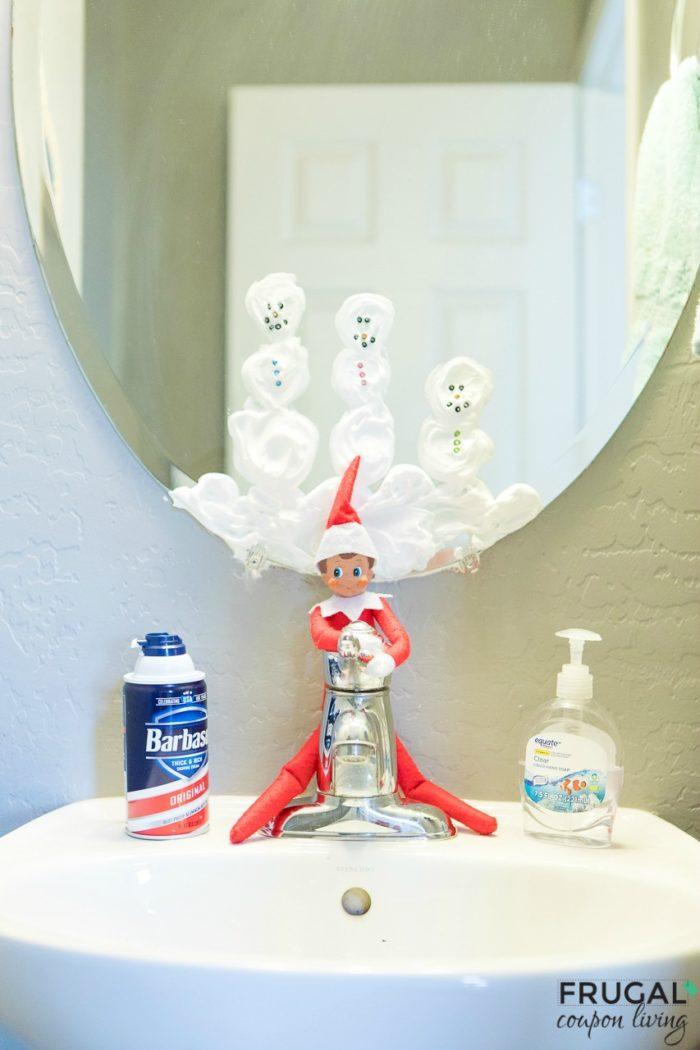 Elf with shaving cream snowmen on mirror.