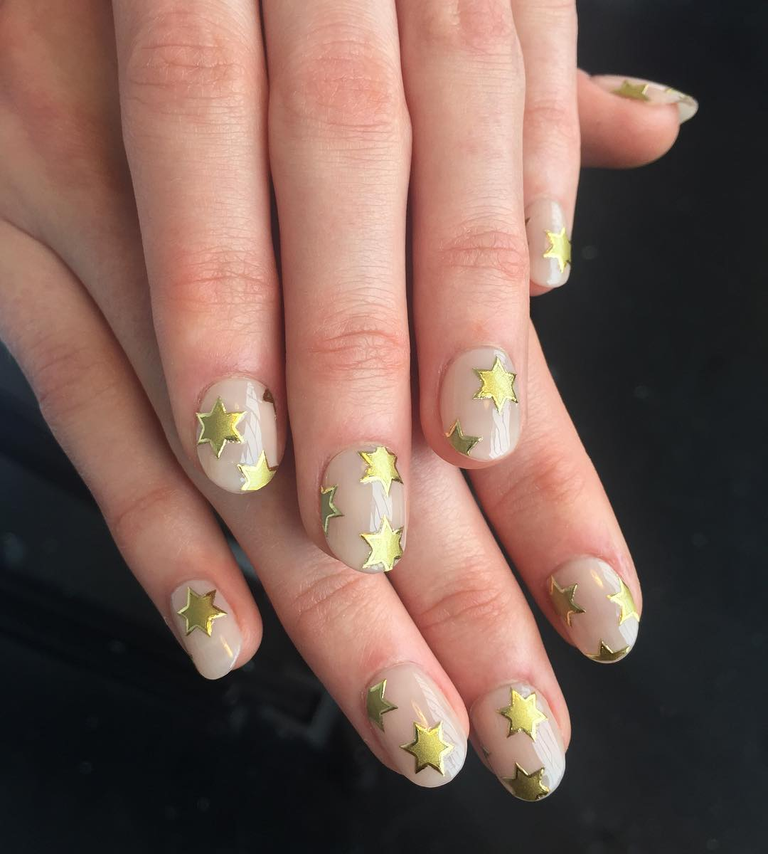 Nude nails with golden stars.