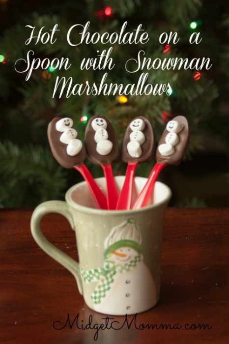 Hot chocolate on a spoon with snowman marshmallows.